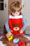 Biscotti adorabili del pane dello zenzero di cottura del ragazzo per il Natale Fotografie Stock Libere da Diritti