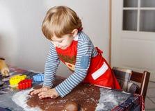Biscotti adorabili del pane dello zenzero di cottura del ragazzo per il Natale Fotografia Stock