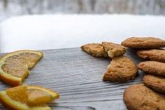 Biscotti arancio rotondi con i frutti canditi variopinti e una fetta di arancia succosa che si trova su una tavola di legno contr fotografie stock