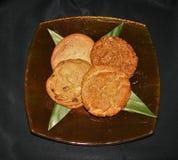 Biscotti assortiti su una lastra di vetro con un fondo nero fotografia stock libera da diritti