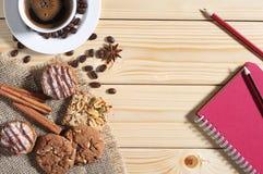 Biscotti, caffè e blocco note su una tavola fotografia stock libera da diritti