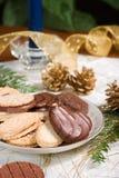 Biscotti, candela blu, filiale dell'abete e coni del pino sul napki di festa Fotografia Stock