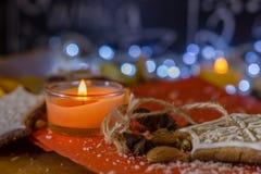 Biscotti, candela, mandorle e spezie dello zenzero di Natale su un fondo rosso e di legno Immagini Stock Libere da Diritti