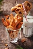 Biscotti or cantucci with milk on wooden rustic table. Christmas or New Year food concept. Biscotti or cantucci with milk on wooden rustic table. Close up stock image