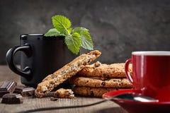 Biscotti casalinghi, cioccolato, ramoscello della menta Tazza rossa e nera con il tè caldo del caffè Copi lo spazio fotografia stock libera da diritti