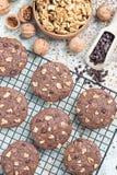 Biscotti casalinghi del cioccolato con le noci e di pepita di cioccolato sulla tavola e sullo scaffale di raffreddamento, vertica Fotografie Stock