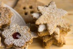 Biscotti casalinghi del linzer e del pan di zenzero con inceppamento, in polvere, nelle forme differenti, su un bordo di legno, l Fotografia Stock