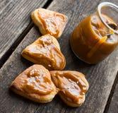 Biscotti con caramello e sesamo salati fondo di legno del vaso del caramello Cuore dei biscotti Fotografie Stock