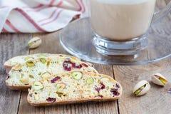 Biscotti con il mirtillo rosso ed il pistacchio, latte della tazza di caffè Fotografia Stock Libera da Diritti