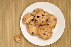Biscotti con l'uva passa sul piatto sulla stuoia della paglia Immagini Stock