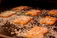 Biscotti con la polvere dello zucchero su un piatto di cottura immagini stock