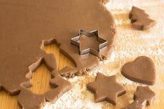 Biscotti d'impastamento del pan di zenzero sulla tavola della plancia Immagini Stock