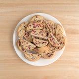 Biscotti de la almendra del arándano con el chocolate blanco en una placa Foto de archivo libre de regalías