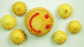 Biscotti del burro con pittura culinaria dipinta con un emoticon divertente e circondata dai piccoli biscotti Movimento in un cer stock footage