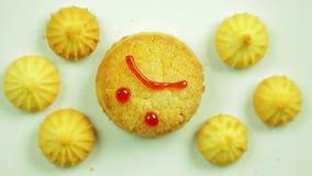 Biscotti del burro con pittura culinaria dipinta con un emoticon divertente e circondata dai piccoli biscotti Movimento in un cer archivi video