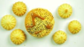 Biscotti del burro con pittura culinaria dipinta con un emoticon divertente e circondata dai piccoli biscotti Movimento in un cer video d archivio