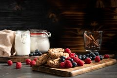 Biscotti del cioccolato accanto ai mirtilli e rasberry fotografie stock