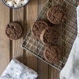 Biscotti del cioccolato alla griglia del metallo, con il tovagliolo e la tazza vicino su fondo di legno immagini stock