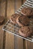 Biscotti del cioccolato alla griglia del metallo su fondo di legno immagini stock