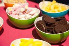 Biscotti del cioccolato, caramelle gommosa e molle e l'altra confetteria in ciotole luminose immagini stock libere da diritti