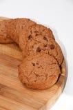 Biscotti del cioccolato sul bordo di legno rotondo Immagini Stock