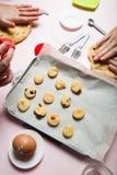 Biscotti del cuoco della figlia e della mamma con le bacche della pasta immagini stock