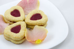 Biscotti del cuore di giorno del ` s del biglietto di S. Valentino con i petali rosa immagine stock