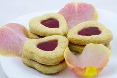 Biscotti del cuore di giorno del ` s del biglietto di S. Valentino con i petali rosa fotografie stock