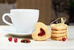 Biscotti del cuore e tazza a forma di di tè Fotografia Stock