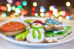 Biscotti del pan di zenzero di Natale su un fondo del bokeh Fotografia Stock