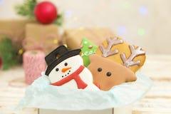 Biscotti del pan di zenzero di Natale nella fine di legno bianca del fondo del contenitore di regalo su Fotografie Stock Libere da Diritti