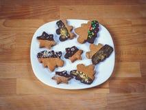 Biscotti del pan di zenzero su fondo di legno Pupazzo di neve, cervo, abete, stivale, Santa Claus, guanto Fotografia Stock
