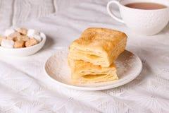 Biscotti del soffio su un vassoio di legno con una tazza di tè Dolci per tè Fotografie Stock Libere da Diritti