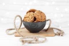 Biscotti deliziosi del cioccolato in un piatto sui precedenti bianchi di legno decorati con una corda Immagine Stock Libera da Diritti