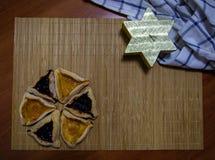 Biscotti dell'inceppamento del mirtillo e dell'albicocca di Hamantash Purim con la candela di legno di forma del fondo della tavo immagine stock