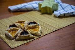 Biscotti dell'inceppamento del mirtillo e dell'albicocca di Hamantash Purim con la candela di legno di forma del fondo della tavo fotografia stock