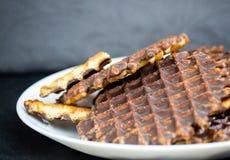 Biscotti della cialda con cioccolato su un fondo nero Immagine Stock