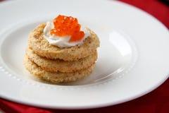 Biscotti della crusca dell'avena con il formaggio cremoso rosso e del caviale Fotografie Stock