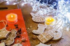 Biscotti dello zenzero con glassa bianca su un fondo di legno rosso e marrone Fotografia Stock Libera da Diritti