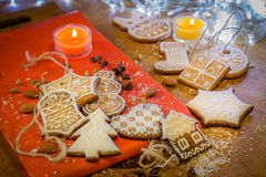 Biscotti dello zenzero di Natale con glassa bianca su un fondo rosso e marrone Immagine Stock