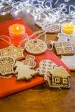 Biscotti dello zenzero di Natale su un fondo rosso e di legno Fotografie Stock
