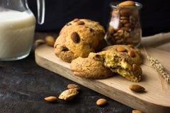 Biscotti di biscotto al burro americani con le gocce di cioccolato e una brocca di latte e di mandorle Fondo scuro di lerciume Lu immagini stock libere da diritti