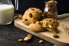 Biscotti di biscotto al burro americani con le gocce di cioccolato e una brocca di latte e di mandorle Fondo scuro di lerciume Lu fotografia stock