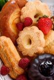 Biscotti di biscotto al burro assortiti con il eclair, il muffin e le bacche fresche immagini stock libere da diritti
