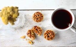 Biscotti di Blackberry con tè su un fondo e su un fiore bianchi Immagine Stock