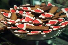 Biscotti di Brown con il cappello di Natale sulla lastra di vetro nel partito di cena Fotografia Stock Libera da Diritti