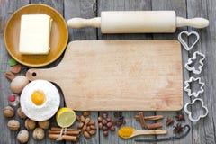 Biscotti di cottura con la scheda di taglio vuota Immagini Stock