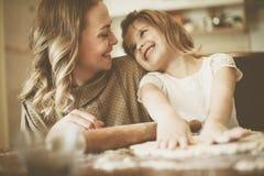 Biscotti di cottura della figlia e della madre immagini stock