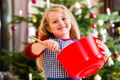 Biscotti di cottura della ragazza davanti all'albero di Natale Immagine Stock Libera da Diritti