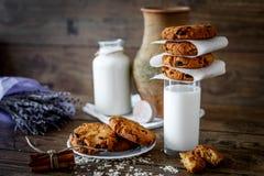 Biscotti di farina d'avena casalinghi con i dadi ed uva passa e bicchiere di latte su fondo di legno scuro, primo piano, fuoco se fotografia stock libera da diritti